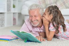 Grandfather reading book with his granddaughter. Grandfather reading book with his little granddaughter Royalty Free Stock Photography