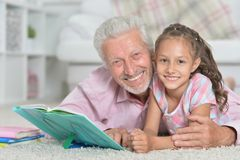 Grandfather reading book with his little granddaughter. Portrait of grandfather reading book with his little granddaughter Stock Photo