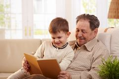 Grandfather reading book to grandson. Happy grandfather sitting in armchair and reading book to his grandson, smiling Stock Images