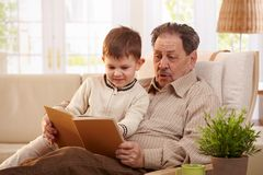 Grandfather reading book to grandson. Grandfather sitting in armchair holding his grandson. and reading book together Royalty Free Stock Images