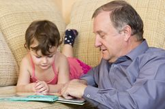 Grandfather reading with granddaughter Royalty Free Stock Image
