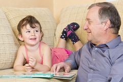 Grandfather reading with grandniece Stock Images