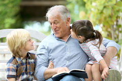 Free Grandfather Reading Story To Grandchildren In The Garden Stock Photography - 64655152