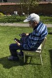 Grandfather Reading Tablet Internet Garden. Old Man Royalty Free Stock Photos