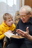 Grandfather Reading To His Grandson. Grandfather reading book aloud to his grandson, who is listening to him with attention Royalty Free Stock Photography