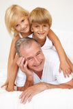 Grandfather Relaxing On Bed With Grandchildren Stock Photography