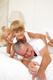Grandfather Relaxing On Bed With Grandchildren Royalty Free Stock Photography