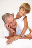 Grandfather Relaxing On Bed With Grandson Royalty Free Stock Photo