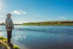 Grandfather on the riverbank catches fish. A fisherman stands on the river bank and catches fish in the nature Royalty Free Stock Photo