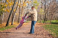 Grandfather rotates  granddaughter  in wood Stock Images