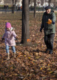 Grandfather run his niece in a park in autumn. Stock Image