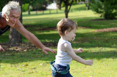 Grandfather running after grandson & having fun outdoors in park Royalty Free Stock Photos