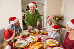 Grandfather in santa hat carving roast turkey at christmas Stock Images