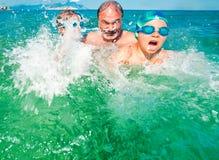 Grandfather sea vacation kids fun splashing Stock Photos
