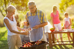 Grandfather serving food from barbecue grill Stock Image