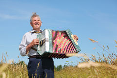 Grandfather in shirt play on accordion Stock Photo