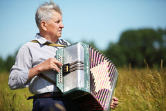 Grandfather in shirt play on accordion Stock Photos
