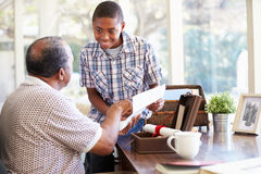 Grandfather Showing Document To Grandson Stock Images