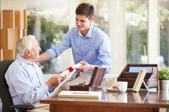 Grandfather Showing Document To Teenage Grandson Stock Photo