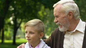 Grandfather showing his grandson something in park, enjoying free time together stock footage