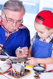 Grandfather showing PCB soldering to grandchild Royalty Free Stock Photos