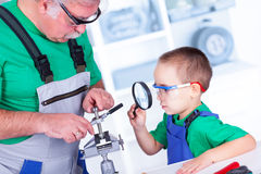 Grandfather showing to grandchild the thread cutting die Stock Image