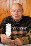 The grandfather sits at a table on which to lie the calculator and money, paper notes and coins. He holds an energy saving lamp in hand. Economy of the budget royalty free stock photos