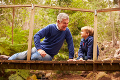 Grandfather sitting with grandson on a bridge in a forest royalty free stock photo