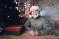 Grandfather is sitting near Cristmas tree in Santa Claus`s hat at night at home. stock photo