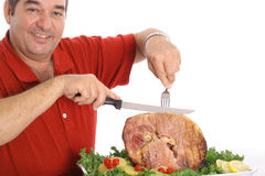 Grandfather slicing a ham Stock Photos