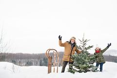 Grandfather and small girl getting a Christmas tree in forest. Grandfather and a small girl getting a Christmas tree in forest, having fun. Winter day Royalty Free Stock Photos
