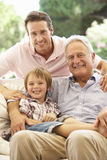 Grandfather With Son And Grandson Laughing Together On Sofa Stock Image