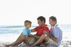 Grandfather, Son And Grandson Relaxing On Sandy Beach Stock Images