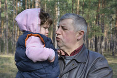 Grandfather soothes little distressed granddaughter. Royalty Free Stock Photos