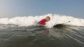 Grandfather is a surfer. Old active healthy man swims on a surfboard