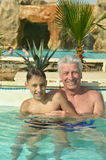 Grandfather swimming with grandson Stock Photo