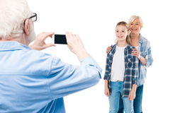 Grandfather taking photo of grandchild and grandmother Stock Photos