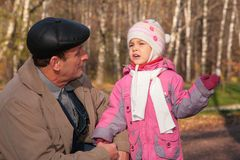 Grandfather talks  with granddaughter in wood Royalty Free Stock Image