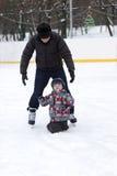 Grandfather teaches his grandchild to skate Stock Photos