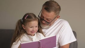 Grandfather teaches his granddaughter to read books. Family educational concept. An elderly man and a little girl leaf