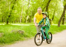 Grandfather teaches his grandson to ride a bike.  royalty free stock image