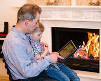 Grandfather teaches his grandson to use a tablet computer Royalty Free Stock Image