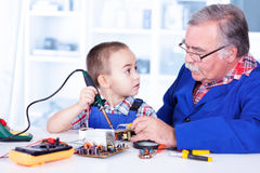 Grandfather teaching grandchild working with soldering iron Royalty Free Stock Photos