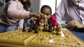 Grandfather teaching grandchildren chess at home stock footage