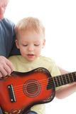 Grandfather teaching grandson play on guitar. Grandfather teaching grandson play on acoustic guitar. Over white background Stock Images