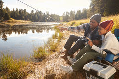 Grandfather Teaching Grandson To Fish By Lake Royalty Free Stock Images