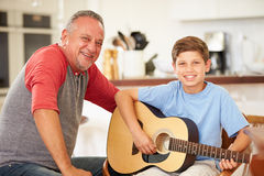 Grandfather Teaching Grandson To Play Guitar Stock Image