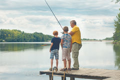 Grandfather Teaching Grandsons To Fish Stock Photography