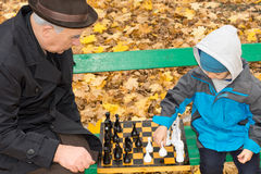 Grandfather teaching his grandson chess Stock Images