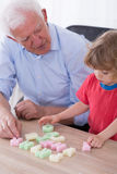 Grandfather teaching preschooler alphabet Royalty Free Stock Images